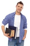Portrait of male student with books smiling. Portrait of male student standing with books in hands, smiling Royalty Free Stock Image