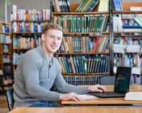 Portrait male student with laptop in the university library Royalty Free Stock Photo