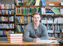 Portrait male student with open book working in a library.  Royalty Free Stock Photography
