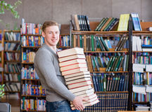 Portrait of a male student with pile books in college library.  Royalty Free Stock Photos