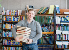 Portrait of a male student with pile books in college library royalty free stock image