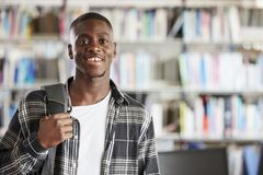 Portrait Of Male Student Standing In College Library Royalty Free Stock Images