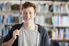 Portrait Of Male Student Standing In College Library Royalty Free Stock Photo