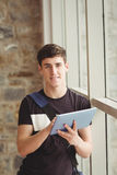 Portrait of male student using digital tablet. While leaning on window in college Royalty Free Stock Photo