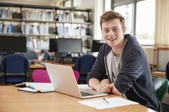 Portrait Of Male Student Working At Laptop In College Library Stock Photos