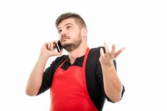 Portrait of male supermarket employer gesturing at phone. Isolated on white background Stock Photography
