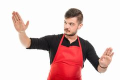 Portrait of male supermarket employer holding something. With both hands like mime concept isolated on white background Royalty Free Stock Photography