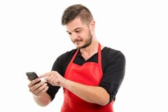 Portrait of male supermarket employer texting on smartphone. With index finger isolated on white background Stock Photo