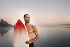 Portrait of a Male Surfer. Portrait of a young attractive male surfer watching the sunset, while holding his board Royalty Free Stock Photos