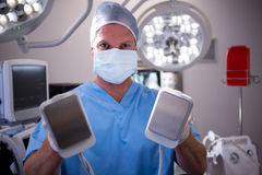 Portrait of male surgeon holding defibrillator. At the hospital Stock Images