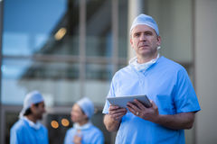 Portrait of male surgeon holding digital tablet. At hospital Royalty Free Stock Images