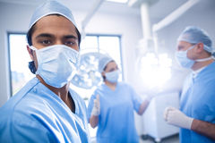 Portrait of male surgeon looking at camera while colleagues interacting in background Stock Photo