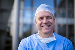 Portrait of male surgeon smiling at camera. In hospital corridor Royalty Free Stock Image