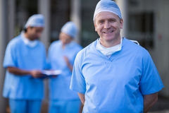 Portrait of male surgeon smiling at camera. In hospital corridor Stock Photography