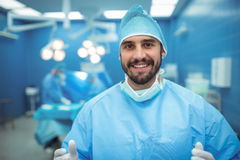 Portrait of male surgeon smiling in operation theater. At hospital Stock Images
