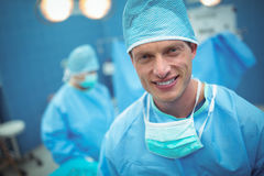 Portrait of male surgeon smiling in operation theater. At hospital Stock Photography