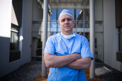 Portrait of male surgeon standing with arms crossed. In hospital corridor Stock Images