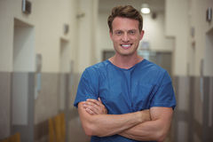 Portrait of male surgeon standing in corridor. Portrait of male surgeon standing with arms crossed in corridor Royalty Free Stock Photo