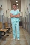 Portrait of male surgeon standing in corridor. Portrait of male surgeon standing with arms crossed in corridor Stock Photography