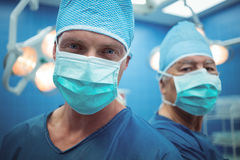 Portrait of male surgeons wearing surgical mask in operation theater. At hospital Royalty Free Stock Photos