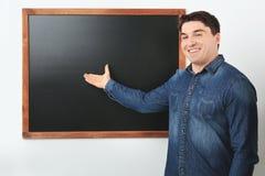 Portrait of male teacher near chalkboard. In classroom Stock Image