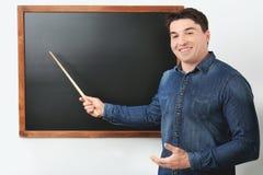 Portrait of male teacher with pointer near chalkboard. In classroom Stock Photo