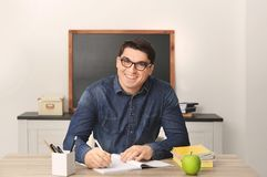 Portrait of male teacher sitting at table. In classroom Royalty Free Stock Images