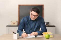 Portrait of male teacher sitting at table. In classroom Royalty Free Stock Photo