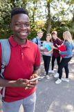 Portrait Of Male Teenage High School Student Outdoors With Friends Holding Mobile Phone stock image