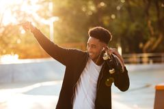 Portrait of a male teenager guy holding skateboard. On shoulders and looking at sunset outdoors Royalty Free Stock Photo