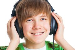 Portrait of a male teenager listening to music. Close-up portrait of a male teenager listening to music with headphone. Isolated on white Royalty Free Stock Images