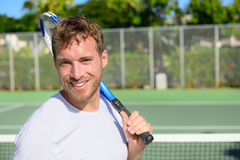 Portrait of male tennis player after playing. Portrait of male tennis player holding tennis racket after playing at game outside on hard court in summer. Fit man Royalty Free Stock Image