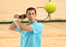 This is my ball. Portrait of a male tennis player with racket ready to hit the ball on a clay court Stock Photos