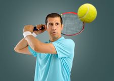 This is my ball. Portrait of a male tennis player with racket ready to hit the ball isolated over gray background Royalty Free Stock Images