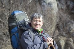 Portrait of a male tourist with a large backpack on the backgrou. Nd of rocks Royalty Free Stock Photography
