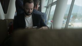 Portrait of male traveller who is writing an email on his smartphone in the airport. stock video