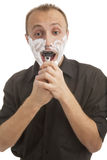 Portrait of a male trying to shave against white Stock Images