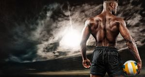 Portrait of afro-american sportsman, beach volleyball player with a ball over sunset. Fit young man in sportswear Royalty Free Stock Image