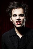 Portrait of a male vampire showing his teeth. Blood is flowing down at the side of his lip Stock Images
