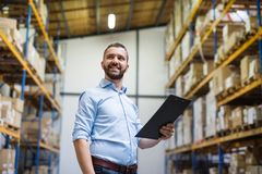 Portrait of a male warehouse worker or supervisor. Portrait of a male warehouse worker or a supervisor holding notes Stock Images