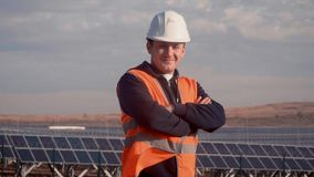 Portrait of a male white engineer solar power plant turns to the camera and smiles. Satisfied with the result, the smile. On her face. on the background of the stock video