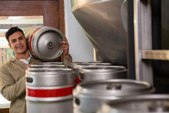 Portrait of male worker carrying keg. Portrait of smiling male worker carrying keg at warehouse Royalty Free Stock Photos