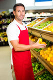 Portrait of male worker holding fruits. In grocery store Royalty Free Stock Images