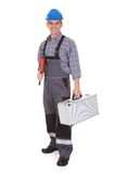 Portrait of a male worker holding worktool. Happy Male Worker Holding Worktool Over White Background Royalty Free Stock Photography