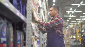 Portrait of a male store worker in a plaid shirt and overalls stock footage