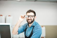 Portrait of a male worker at the printing manufacturing. Portrait of a male worker standing with magnifying glass near the operating desk of the printing Stock Photos