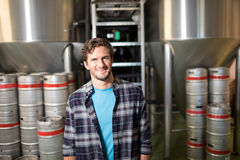 Portrait of male worker standing at factory. Portrait of smiling male worker standing by storage tanks at factory Stock Image