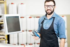 Portrait of a male worker at the printing manufacturing. Portrait of a male worker standing near the operating desk of the printing manufacturing Stock Photo