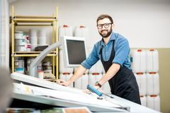 Portrait of a male worker at the printing manufacturing. Portrait of a male worker standing near the operating desk of the printing manufacturing Stock Photos