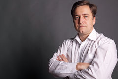 Portrait of the man. In a white shirt on a dark grey background Stock Photos